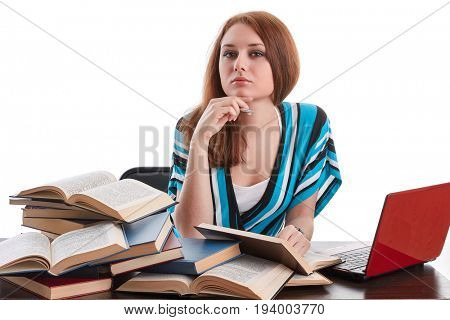 Young woman sitting at a desk   among  books and laptop on a white background.