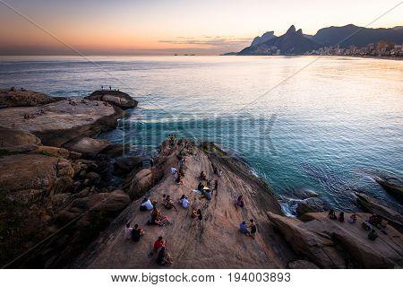 Rio de Janeiro, Brazil - June 30, 2017: People sitting all around on Arpoador rock and enjoying beautiful sunset.