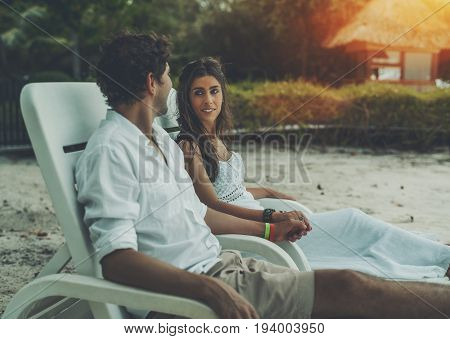 Caucasian beautiful woman and her husband sitting on white beach chairs holding hands of each other and looking into eyes having romantic evening near ocean with bungalow in defocused background