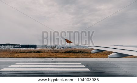 Wide angle view from aircraft window of take-off runway with stripes of zebra airplane wing dry grass and infrastructure of Male international airport overcast sky Indian ocean in background