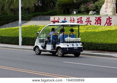 Sanya China April 23 2017 - An open electro car police service with officers inside patrols the roads of Hainan Island