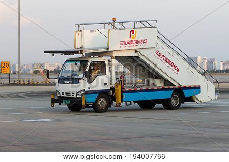 Sanya Hainan China April 25 2017 - IZUZU Cargo Truck with a telescopic ladder installed on it to board passengers on the Phoenix Airport runway