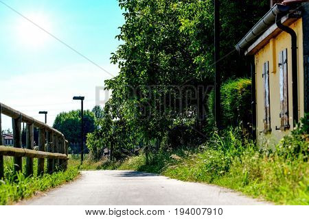 Landscape with the image of a house on chanel bank in a north Italy