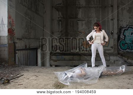 Two Women Are Fighting. One Of Them Is Defeated, The Second Wraps Her Body In Polyethylene