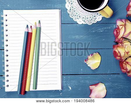 Empty notebook and colorful wooden pencils top view