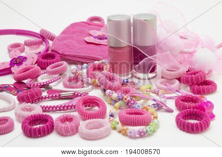 Pink fashion girly hair and nail accessories: clips band and ribbons pins and bow. Teenager hair clippers and grips. Little girl girlie feminine fashion style. Nail polish bottles cosmetic bag