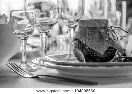 Rustic table setting for a wedding celebration in nice cozy restaurant. Wineglasses, plates and food on table. Guests complement in a rustic jar