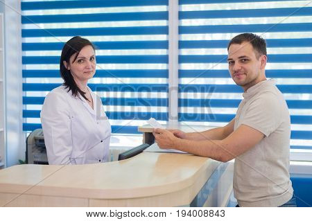 Mid adult female receptionist receiving card from patient in dentist clinic.