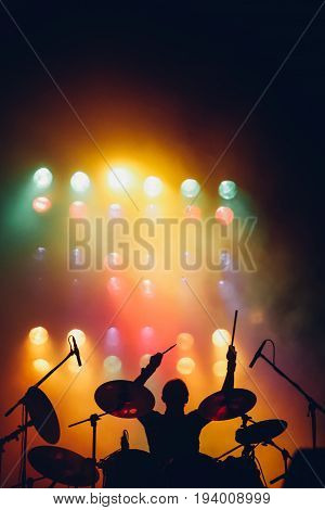 Drummer silhouette at colorful backlights on a stage with the hands raised up with drumsticks
