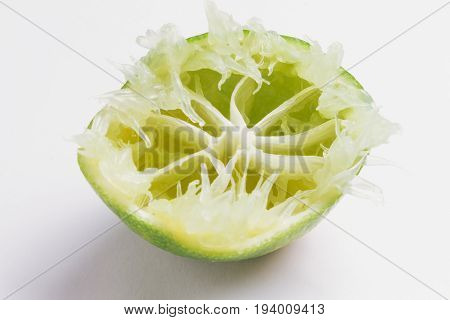 Close Up Of Lime Squeezed On White Background