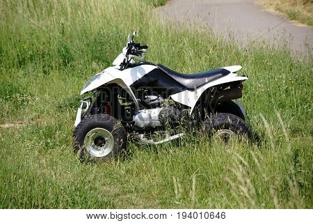 A quad terrain vehicle standing on a meadow in the field.