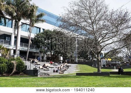 Takapuna Auckland New Zealand (NZ) - August 30 2016: People relaxing and checking their mobile devices in modern urban outdoor furniture