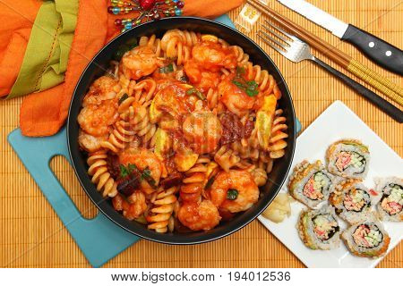 Asian Italian Fusion Pasta Shrimp and Sushi Meal at table.