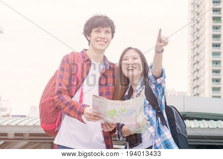Vacation and friendship concept - smiling asian girl and foreign boy friends with city guide map and backpack in city