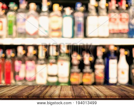 Empty top wooden table with blurred counter bar and bottles Background. For display or montage your products.