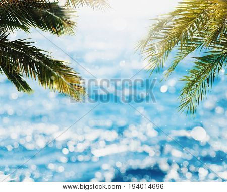 Tropical beach with coconut tree with sunray reflected on the bright sea