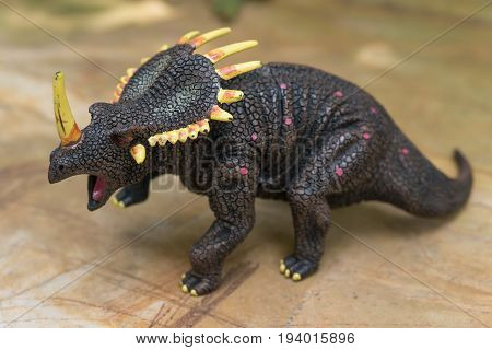 a grey triceratops toy standing on rock