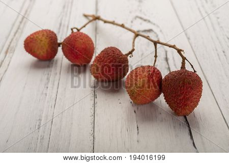 branch of fresh lichees on white wood background