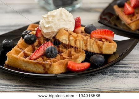 Waffles with whipped cream fresh strawberries and blueberries