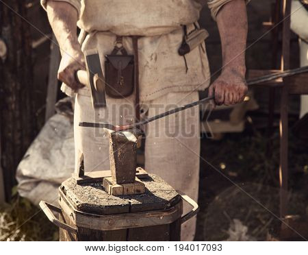 Blacksmith forges part on anvil in antique clothes.