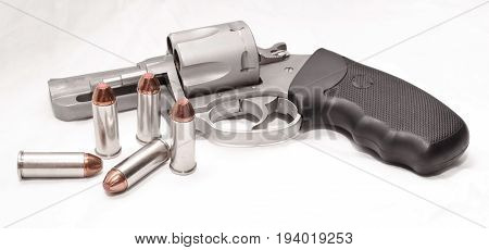 Stainless 44 spl revolver with five bullets in front of it