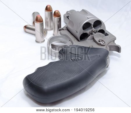 A stainless 44spl revolver unloaded with five bullets next to it