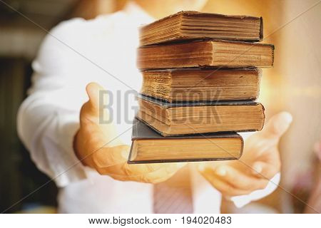 Concept of wisdom book in man's hands in gesture of giving.