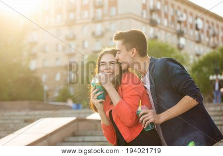 Teenagers drink fruit fresh from glasses. He whispers tender words in her ear. She laughs coquettishly. A couple in love on a date. Romance of first love.