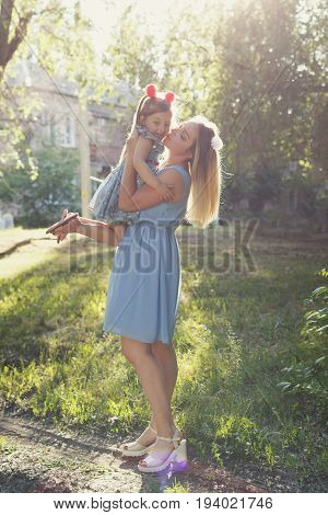 Family values. Mother and daughter. Mother raised the child in her arms. Same dresses and hairstyles. Family look