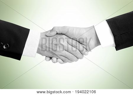 Handshake of businessmen on light green background - greeting dealing merger and a acquisition concepts