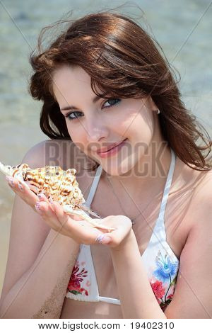beautiful teen girl in swimwear holding a seashell sitting on the beach
