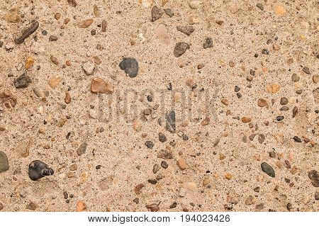 Gray background. Concrete and colored pebbles. Texture with impregnations of sea pebbles