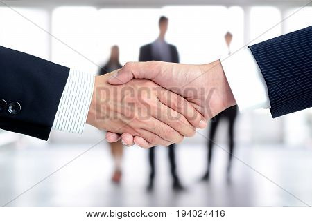 Handshake of businessmen on blur businesspeople background - greeting dealing merger and a acquisition concepts poster