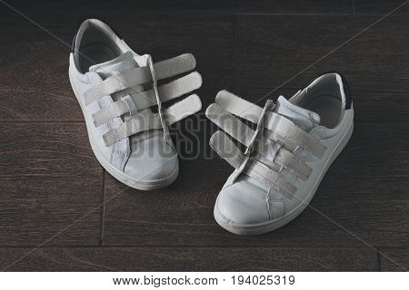 Pair of white worn-out shoes on velcro close-up