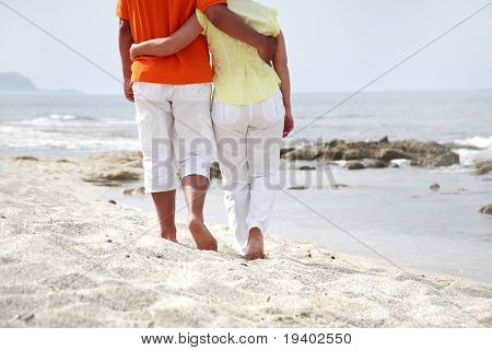 mature couple  in love walking along the beach