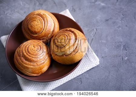 Brown round plate with yummy cinnamon rolls on kitchen table
