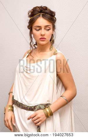 portrait of a beautiful graceful greek young woman in antique white toga