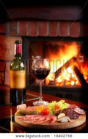 Wine bottle and partially filled glass with assorted food on a wooden serving plate.