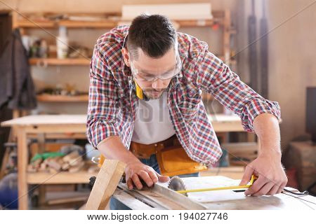 Carpenter taking measurements for working with wooden plank in shop