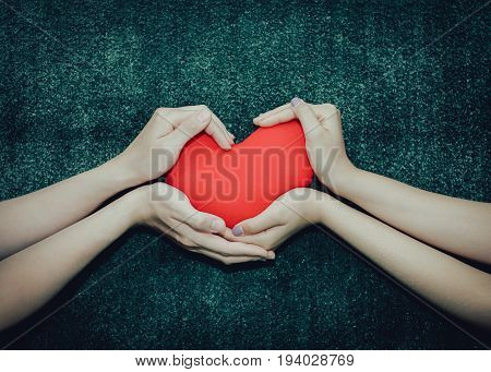 Young man giving a heart-shaped pillow his sweetheart on Valentine's Day. Love beautiful concept