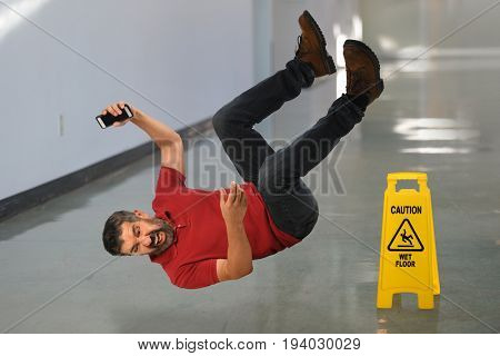 Hispanic businessman falling on wet floor inside building