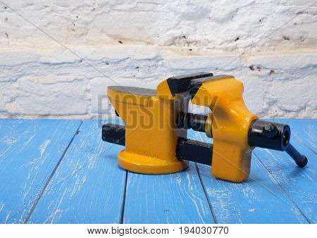 The metalwork tool - Yellow with black a vise on a wooden blue and a white Brickwork background.