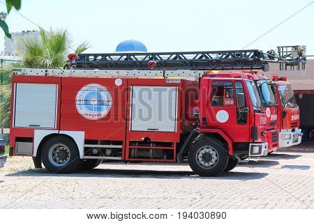 Antalya, Turkey - May 26 2017: Three red firetruck with rescue ladder standing on the street of the city near firehouse