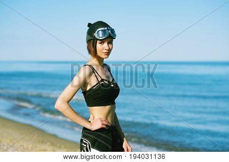 Young stylish girl on the background of the sea in the cap and protective glasses . The model shows sportswear