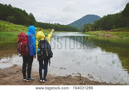 Young couple of hikers planning the route, rear view