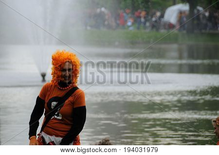 AMSTERDAM, NETHERLANDS - APRIL 30. Man with an orange whig Celebrating Queensday in Amsterdam. Queensday is a popular annual festival celebrating the Queens Birthday.