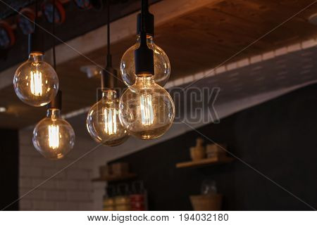 Decorative antique style filament LED light bulbs in restaurant for electricity or technology concept design.