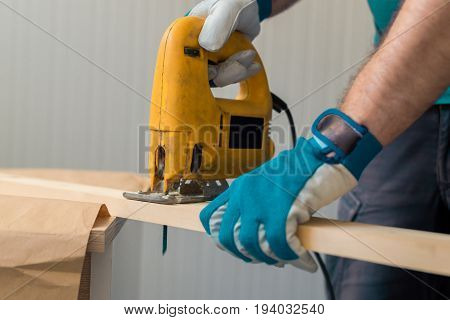Carpenter handyman using electric handy saw on the woodwork workshop table