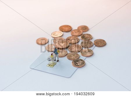 Miniature shoppers with shopping cart figure on a credit card or debit card and a pile of coins background using as shopping e-commerce and online business concept.