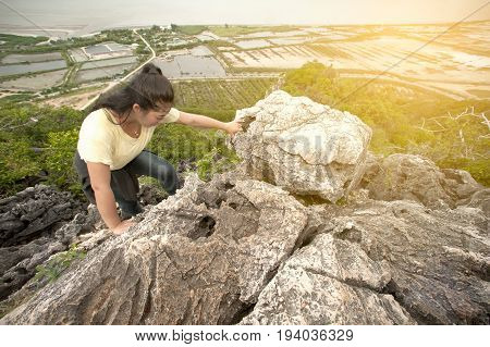 Pretty Asian woman climbing to the peak of  mountains adventure and trekking.